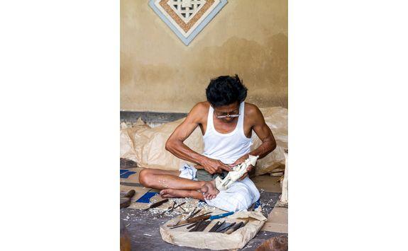 man is making wooden craft