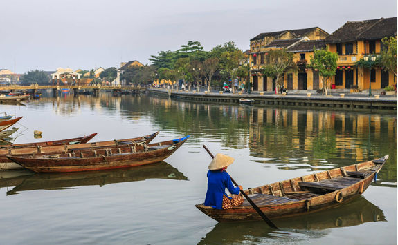 Vietnamese woman padding in old town in Hoi An