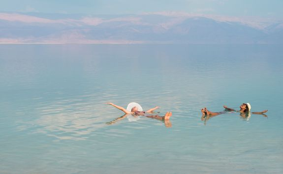 women floating in dead sea