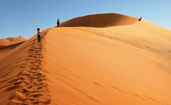 people climbing red sand dunes