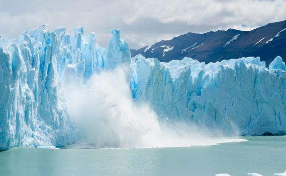 breaking ice falling from glacier