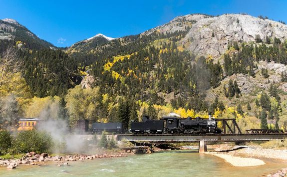 Steam locomotive crossing river and mountain background