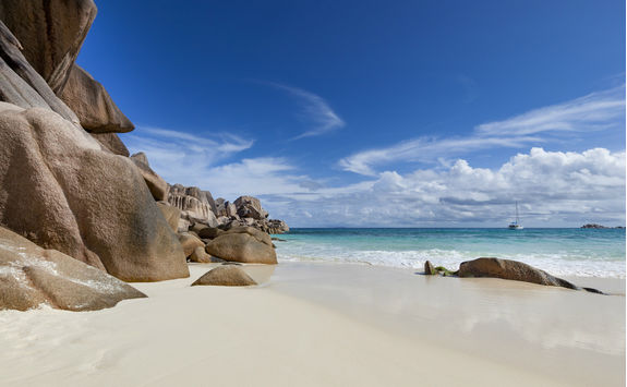 White sand beach and large cliffs in the Seychelles