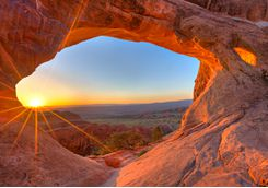 Sun rising through an arch