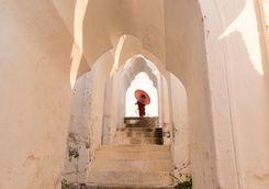 Mandalay Monk walking up white stairs