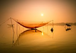 Fishermen with nets at sunset