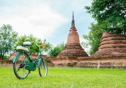 Green bike outside an ancient temple