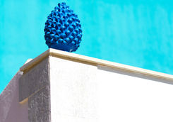 ceramic blue pine cone against turquoise wall