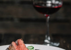 grilled beefsteak with glass of red wine on dark wooden background