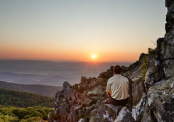 Man watches the sunrise over the Blue Ridge