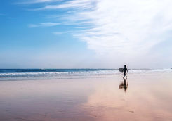 surfer with surfboard walks on cost line bali