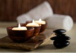 lit candles and black massage stones