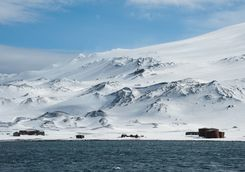 abandoned whaling station with snowy mountain in the background