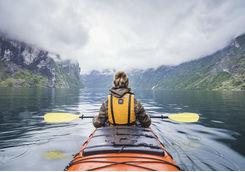Woman kayaking in fjord in Norway
