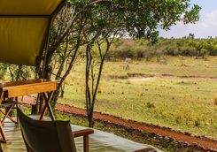 Chairs in front of a canvas tent turned to the savanna
