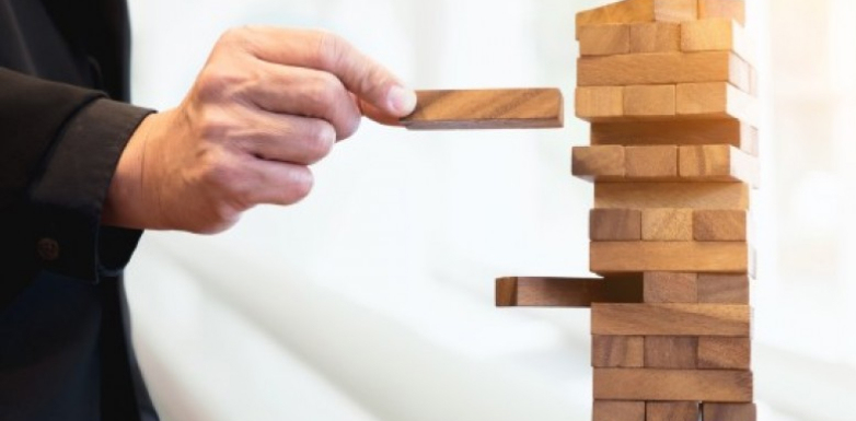A photo of someone removing a block from a jenga tower