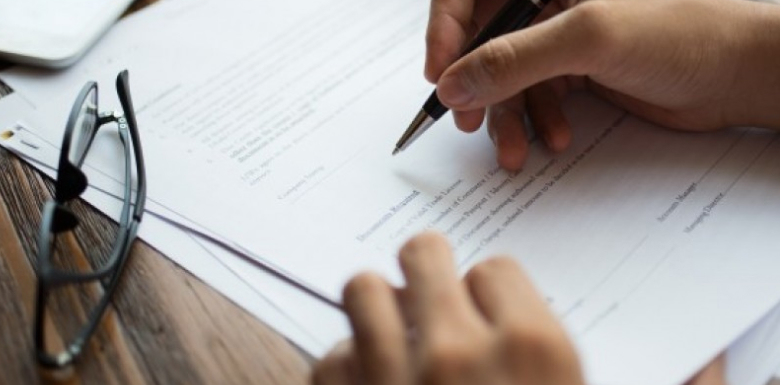 A photo of someone signing important papers