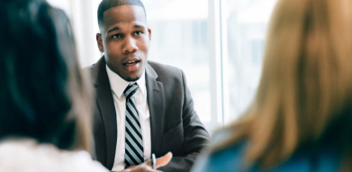 A photo of a man in a suit talking to two others around a meeting room table