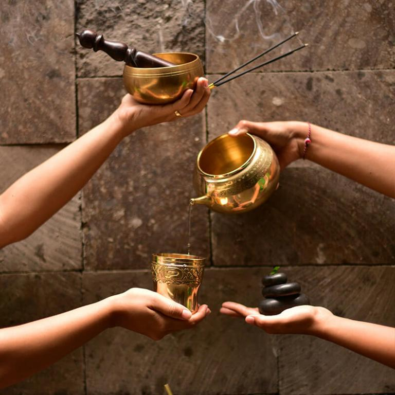 Hands holding gold cups