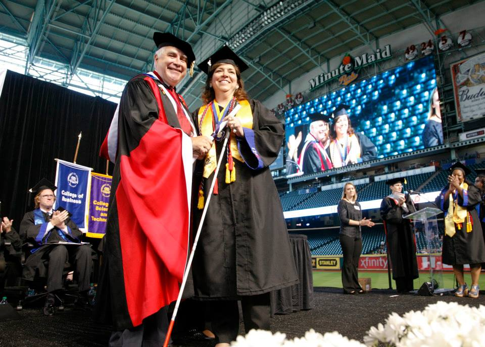 Alma Balleza shakes the hand of UHD President Flores as she walks the stage at commencement.