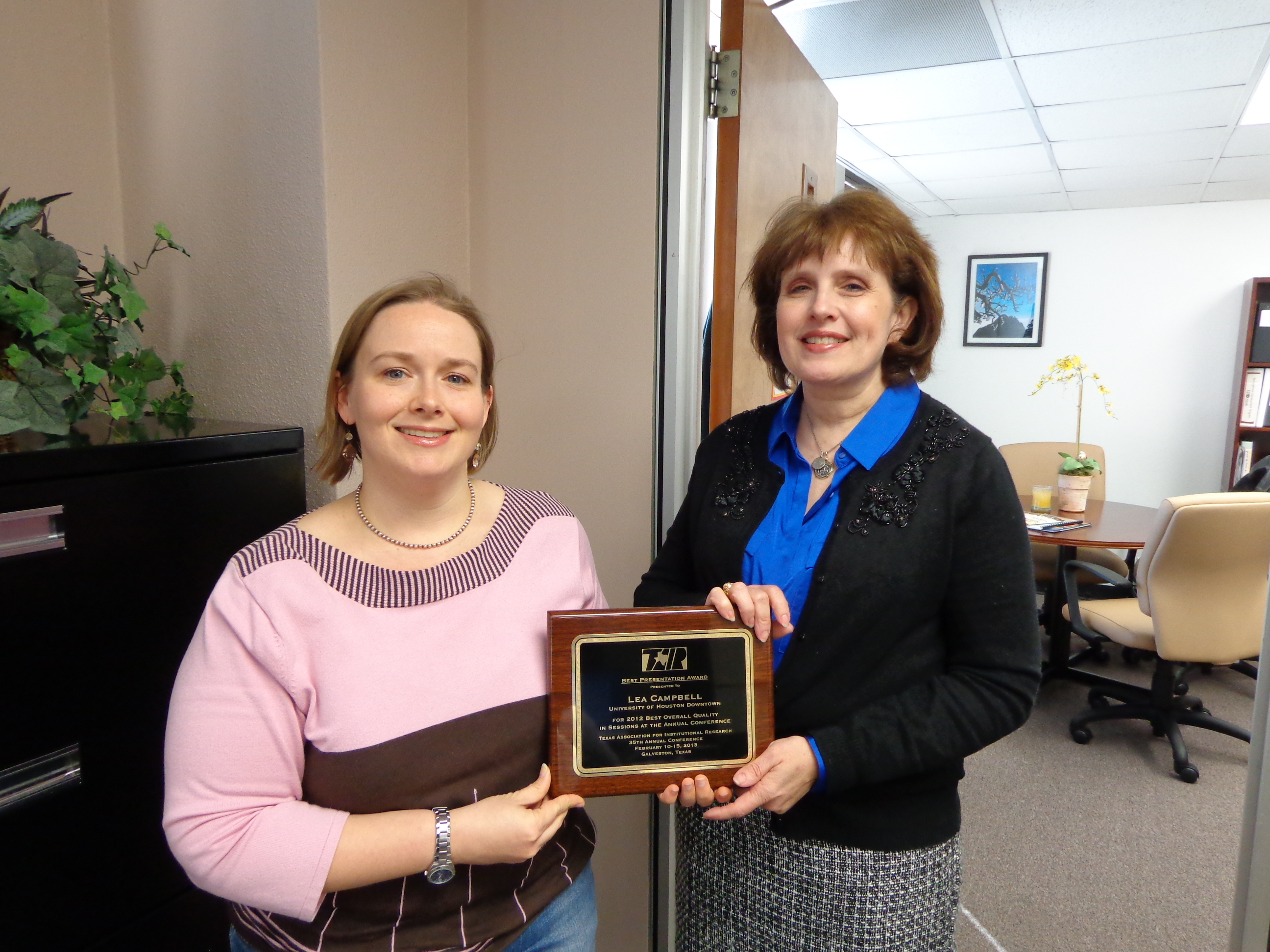 Carol Tucker,  director of Institutional Research and former TAIR president, presents the plaque for Best Presentation to Lea Campbell.