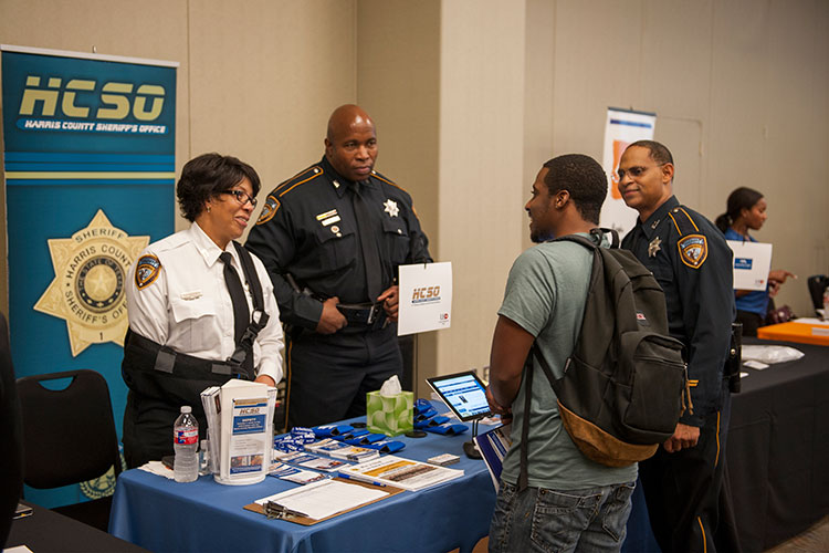 Representatives from the Harris County Sheriff's Office speak to UHD students at fall 2014 career fair