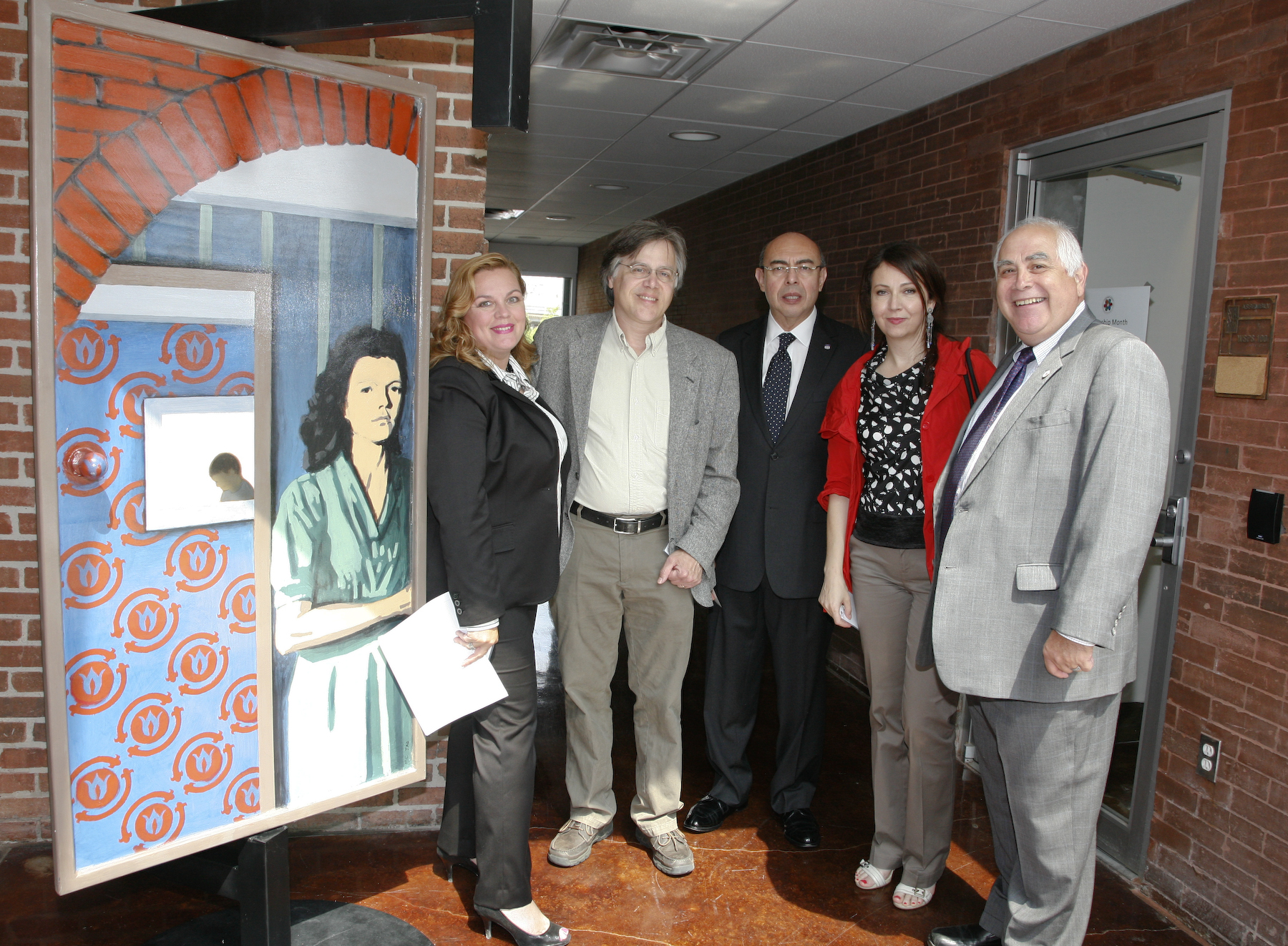 (From left to right):  Dr. Noël Bezette-Flores, Mark Cervenka, Juan Carreon, Karine Parker-Lemoyne and Dr. Bill Flores stand in front of a door painted by Cervenka and French Artist Clément Laurentin for the Texan-French Alliance for the Arts' Open the Door art project.