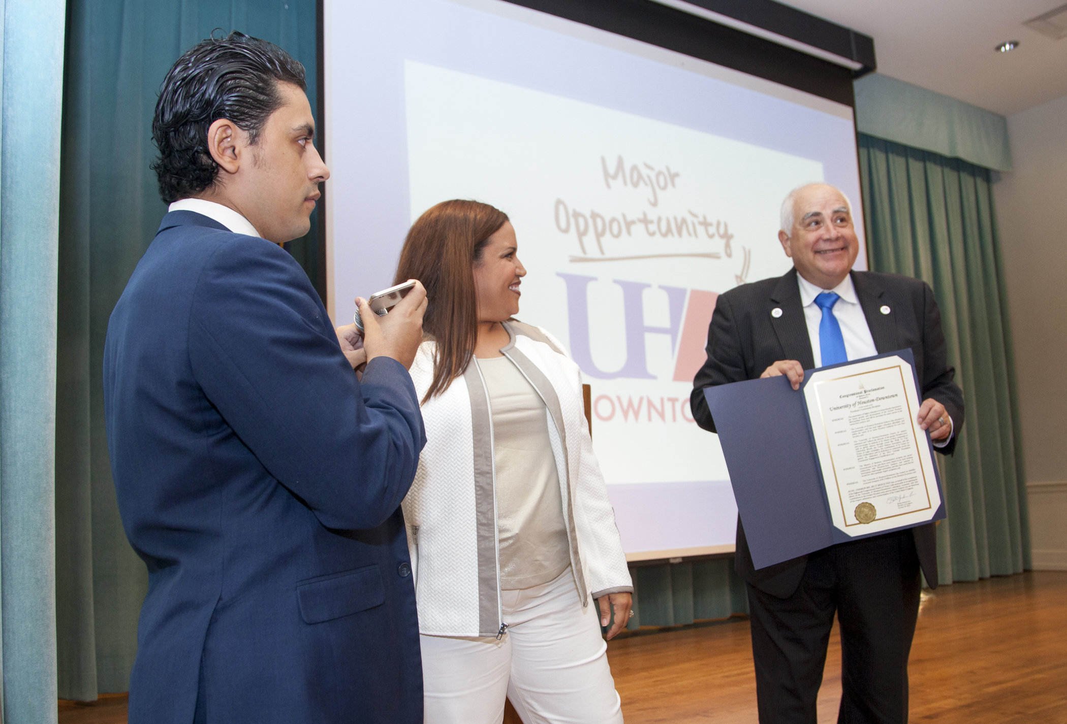 At the President's Community Breakfast Oct. 30, UHD alumnus Ivan Sanchez presents UHD President Bill Flores, Ph.D., with a congressional proclamation on behalf of U.S. Rep. Sheila Jackson Lee as presenter Trazanna Moreno looks on.