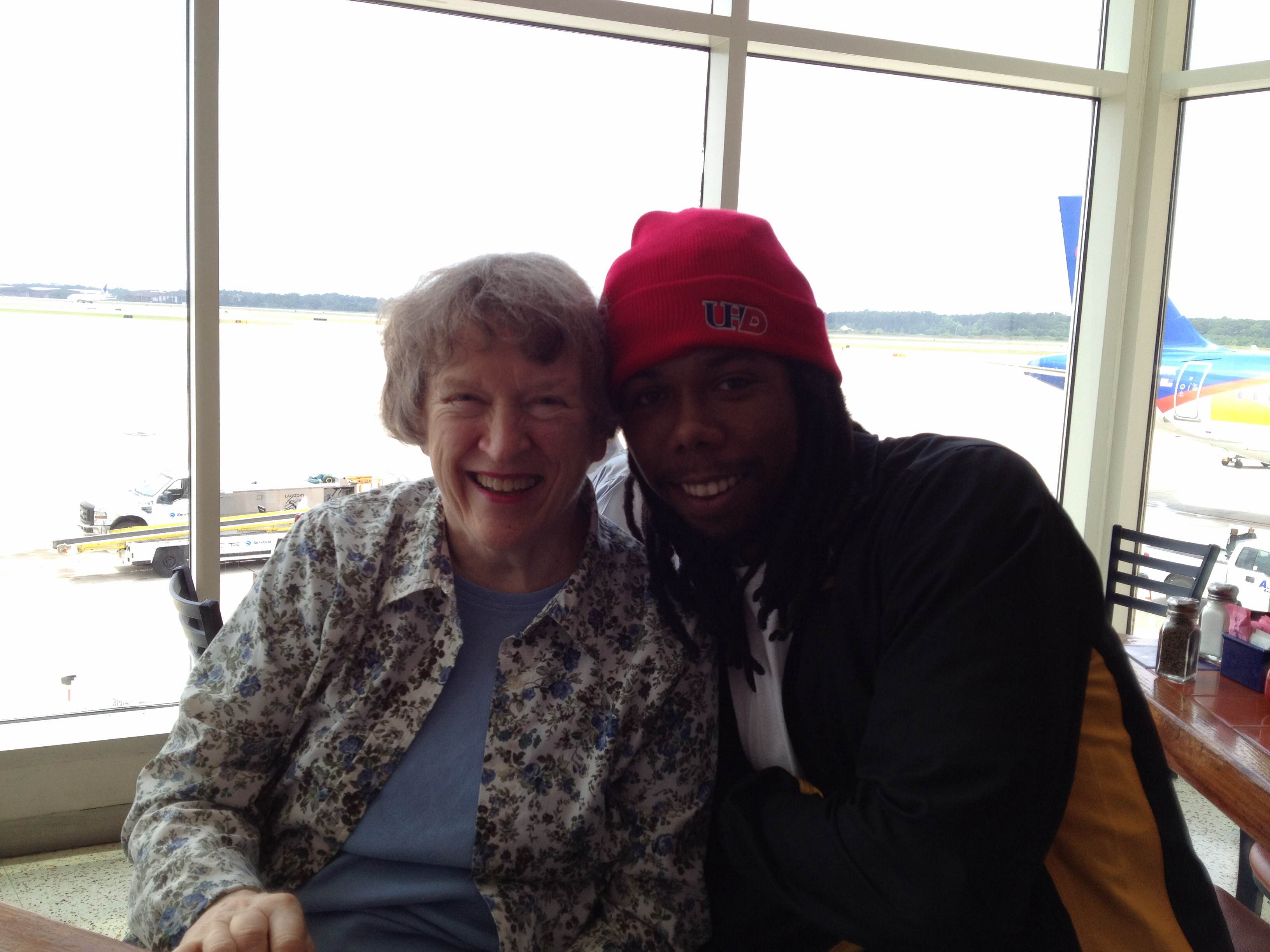 Director Kate Pogue poses with a student at the airport.
