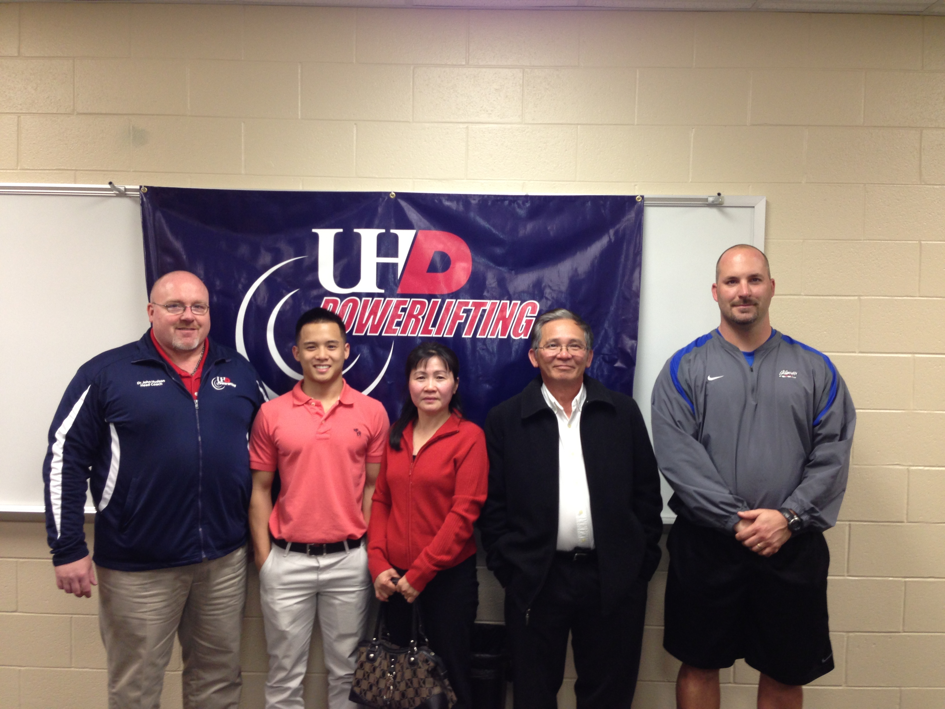 Kenny Nguyen, second from left, stnads with his family, high school coach and UHD Powerlifting Coach John Hudson, left, after signing with UHD and earning a four-year Academic Merit Scholarship.