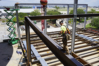 Steel worker walking on curved steel beam at Tampa Airport