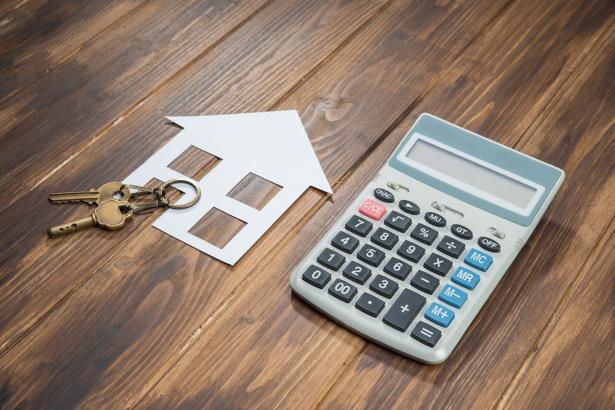 House keys and calculator on wooden floor