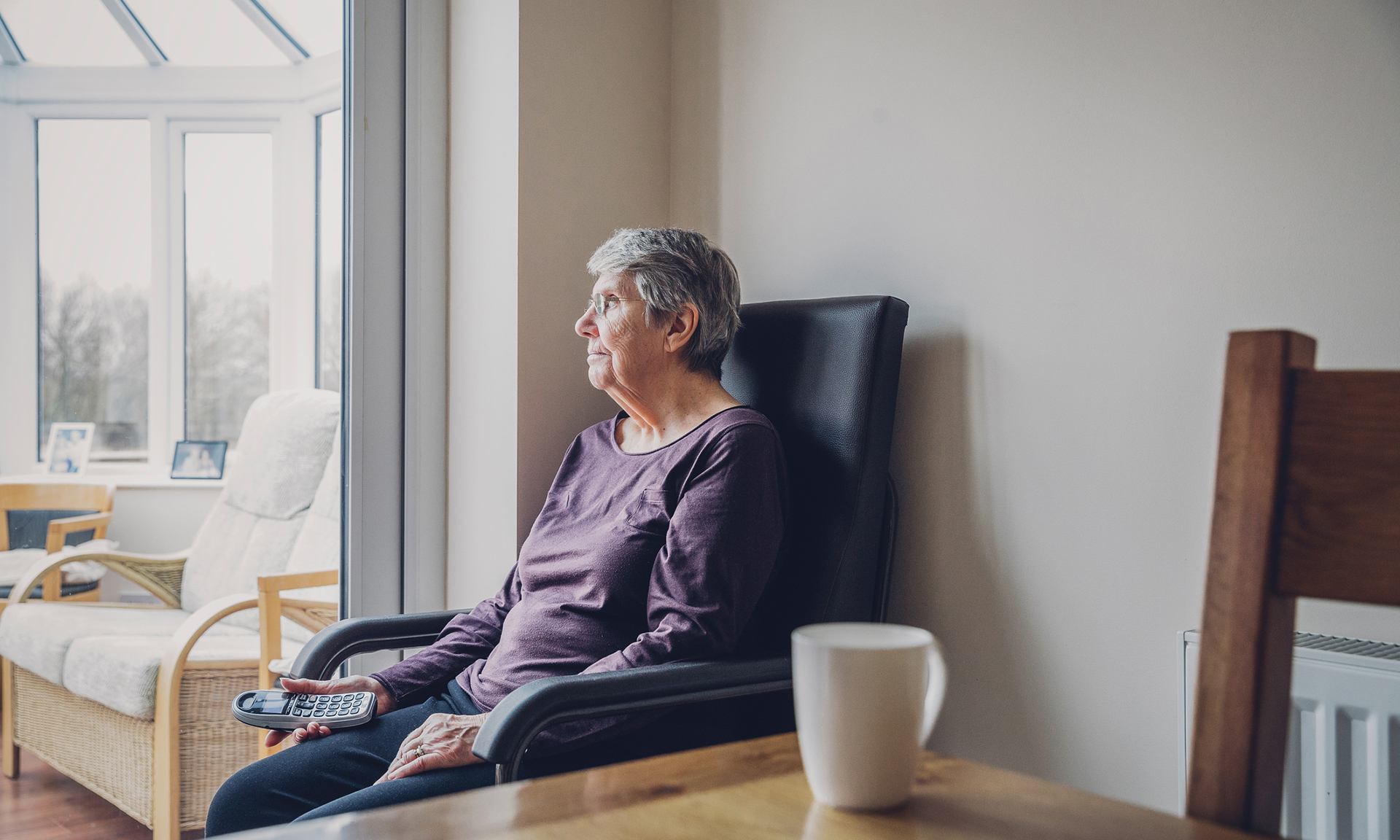 Senior woman sitting alone in her kitchen. She is looking out into her conservatory while holding a home telephone in her hand. Serious expression