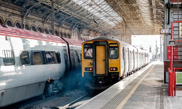 A train leaves the platform. diesel smoke in the air