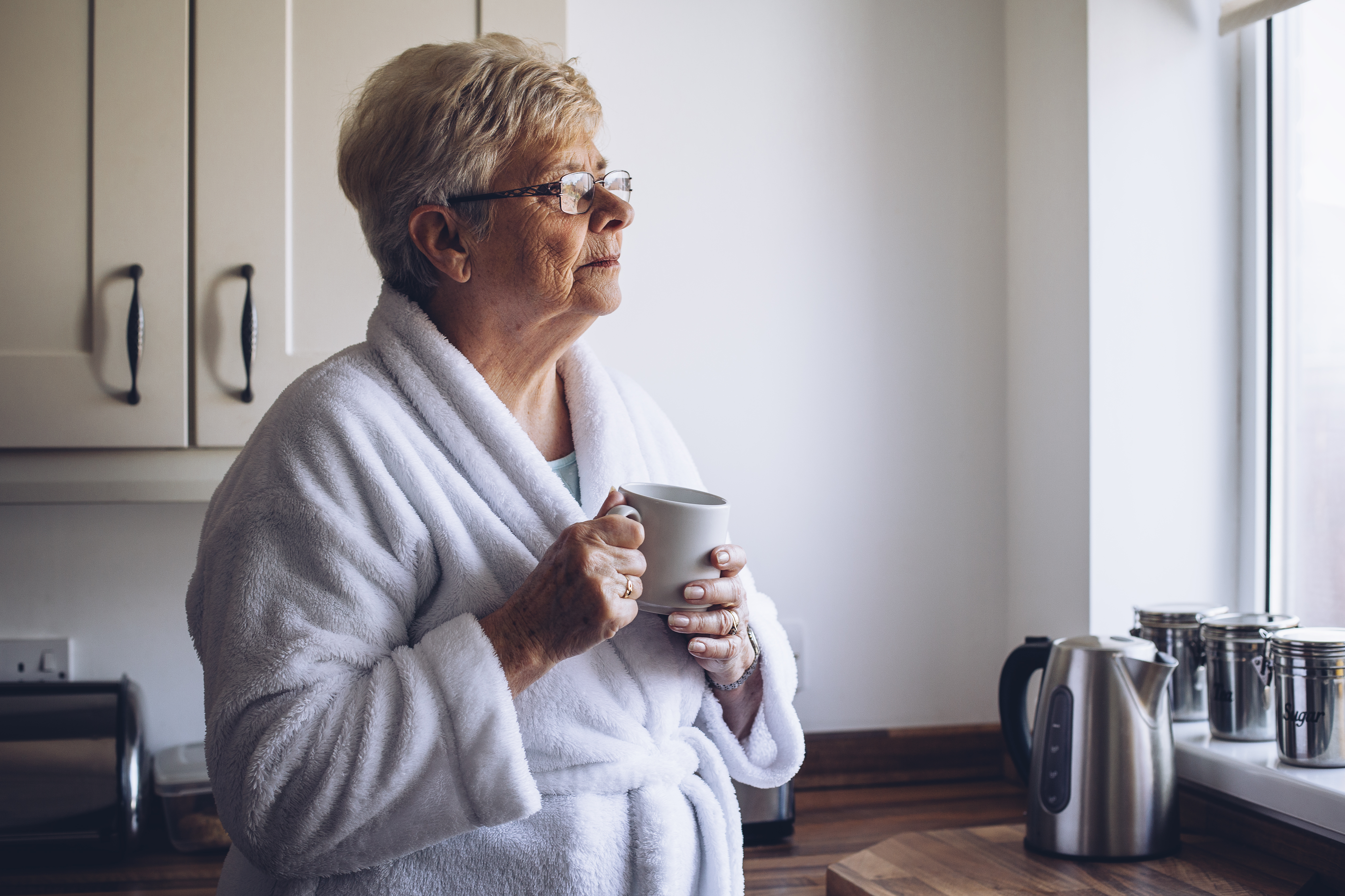 Senior woman looking out of her kitchen window with a cup of tea in hand