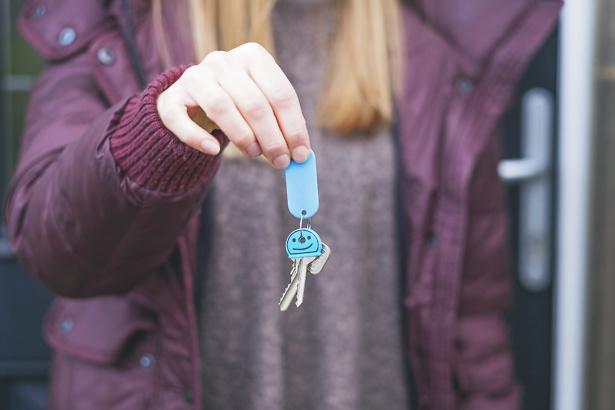Woman holding her new house keys in purple jacket.