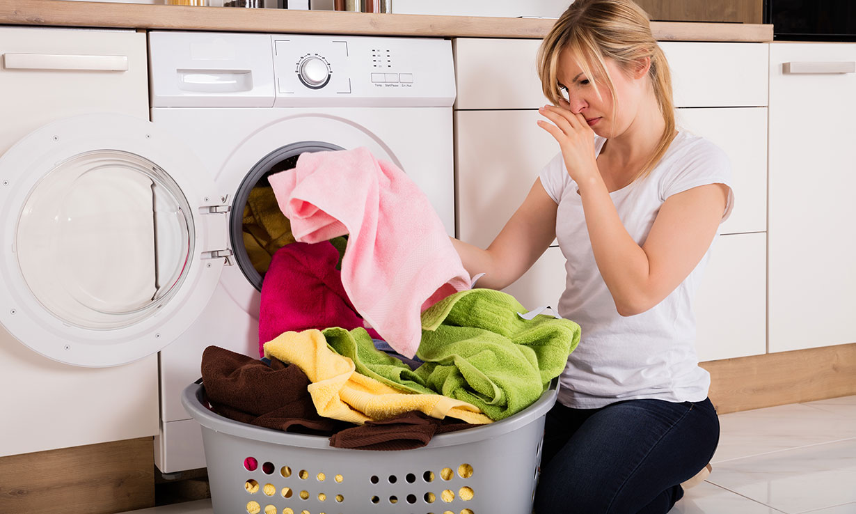 Woman reacting to bad smelling laundry