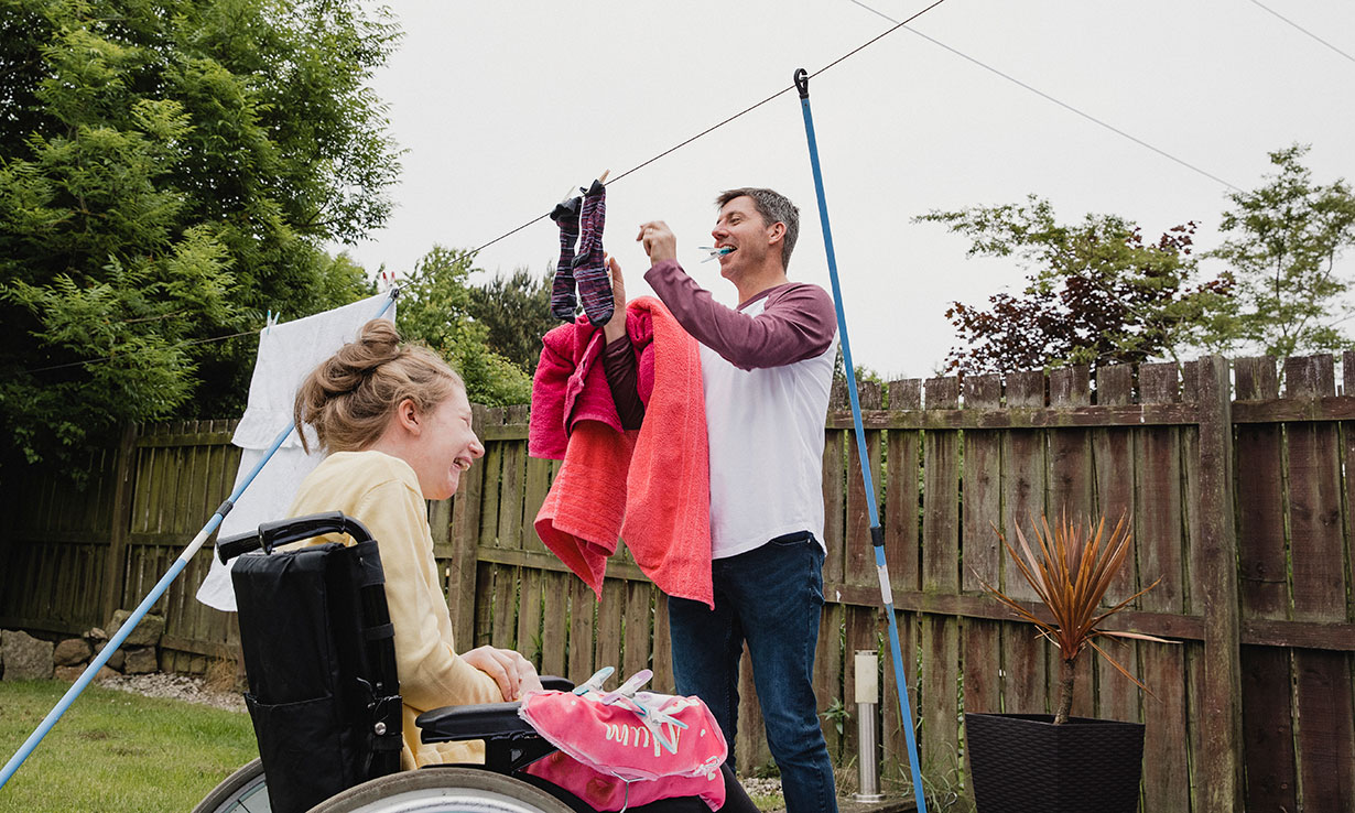 Couple hanging washing up to dry on a line in the garden