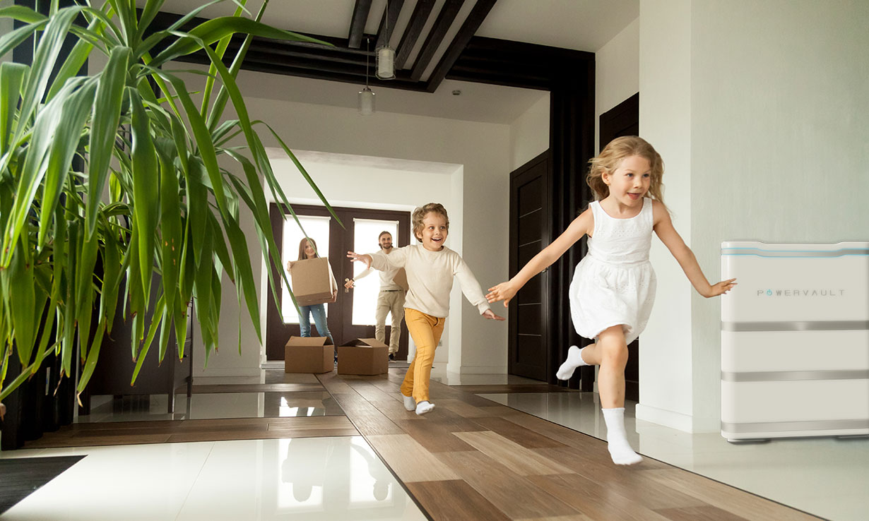Children running through a house with a battery on the wall