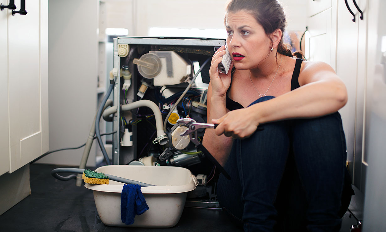 A woman trying to fix a leaking appliance
