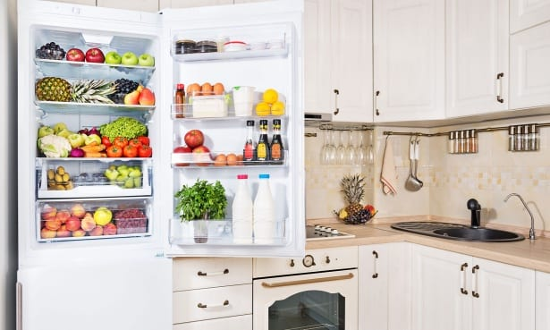The fridge door of a fridge freezer sits open and the fridge freezer is filled with food and drink