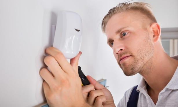 Man installing a burglar alarm sensor