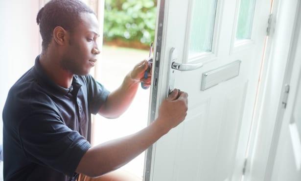 Man installing a door lock on a front door