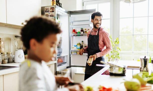 Man standing at an open fridge freezer