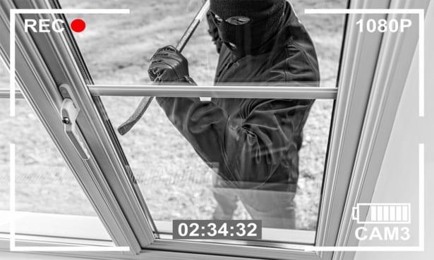 A burglar breaking into a house through a window