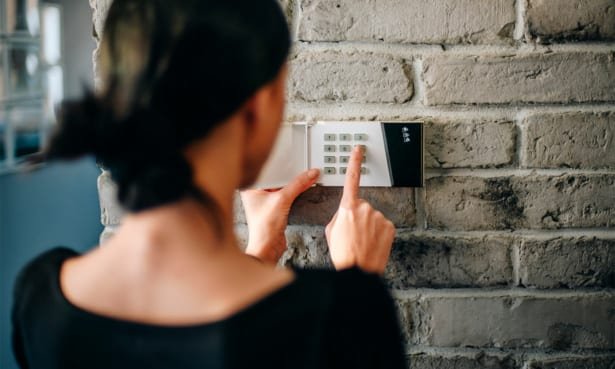 Woman setting a burglar alarm