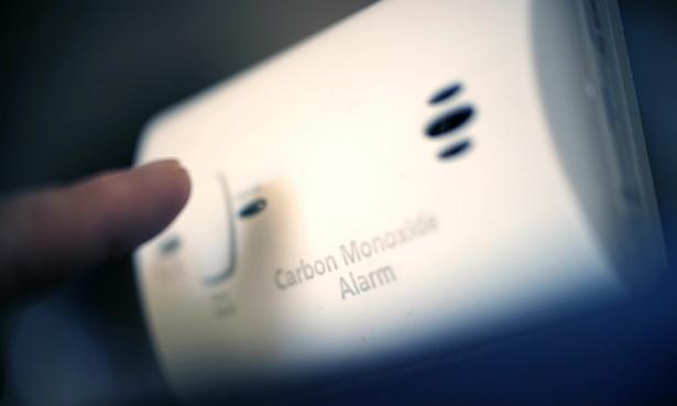Finger about to press a carbon monoxide alarm