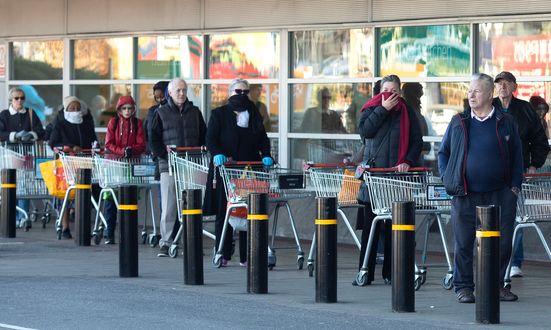 shoppers queuing with trolleys