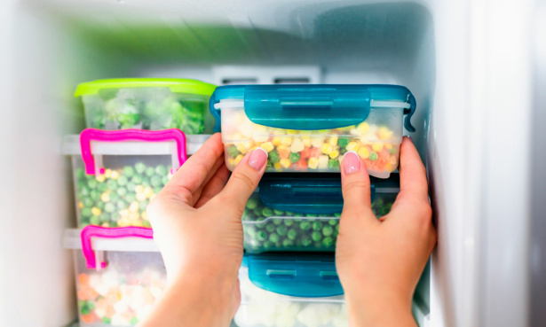 Vegetables in tupperware being slid snugly into the freezer