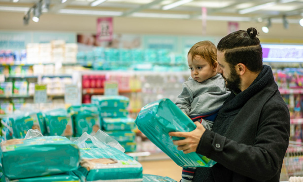Parent with baby buying nappies in a shop